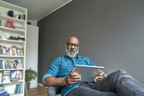 man sitting in chair holding laptop computer